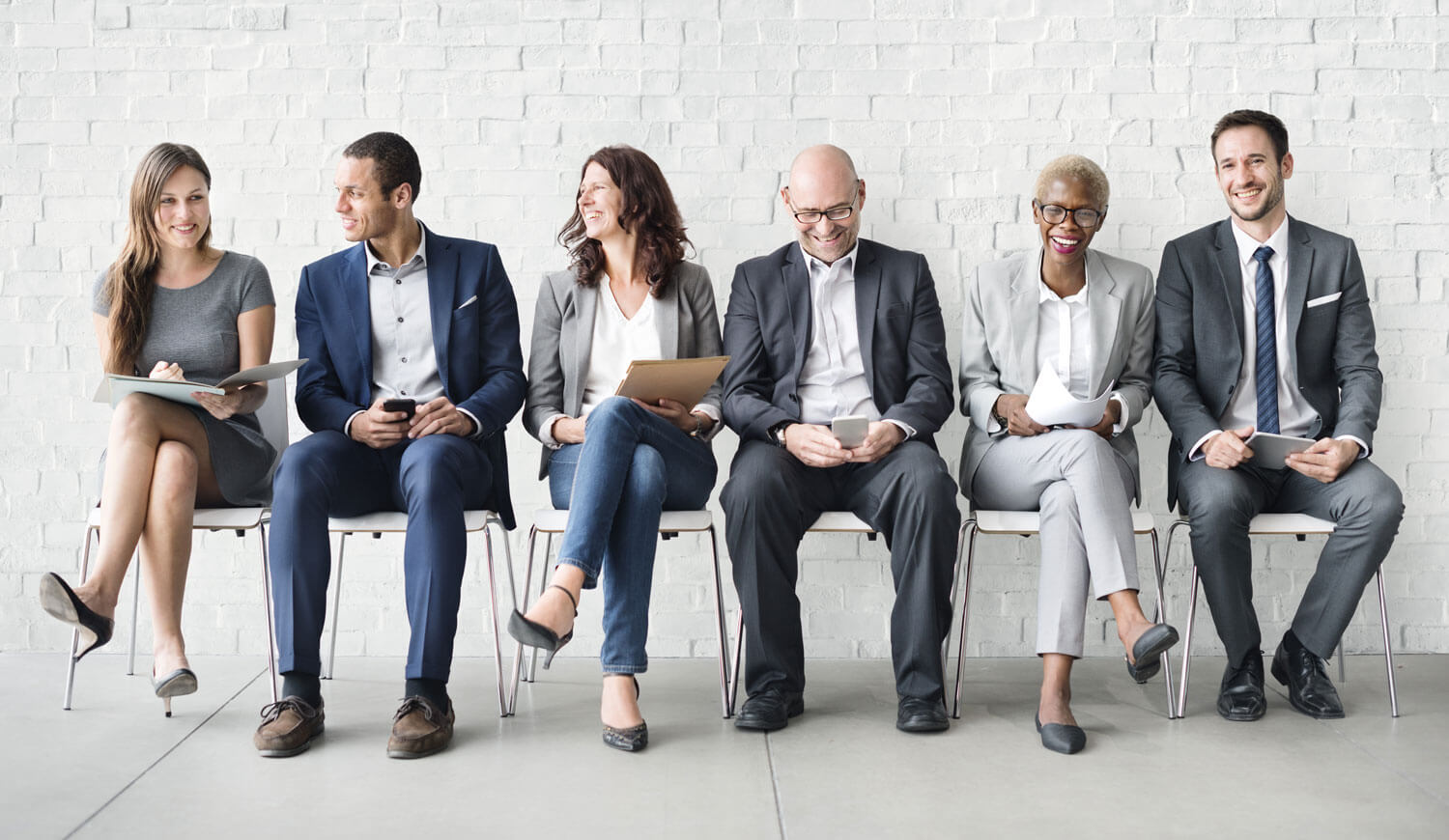 People sitting on chairs waiting for their turn for a recruiting interview for a new job