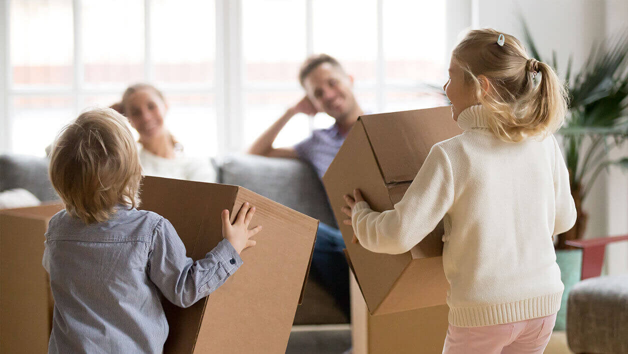 A family just relocated into a new home with kids carrying small moving boxes