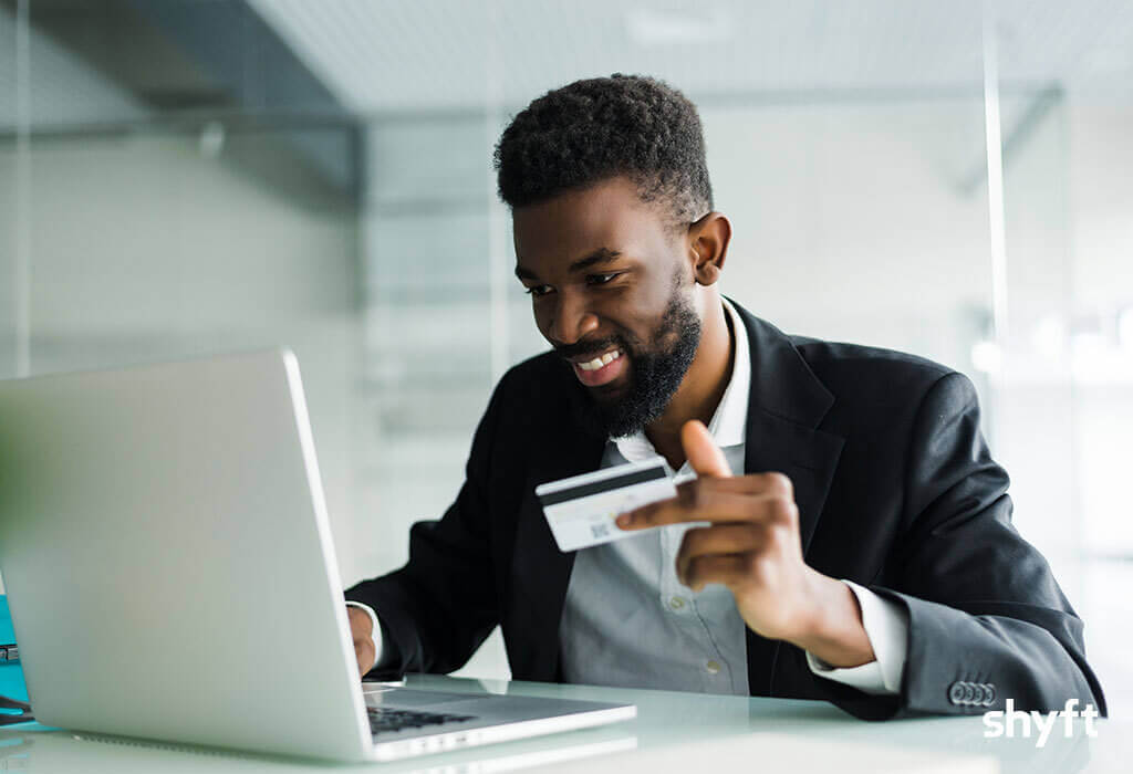 A happy employee holding a ShyftCard for instant payments while checking the payment status on his laptop
