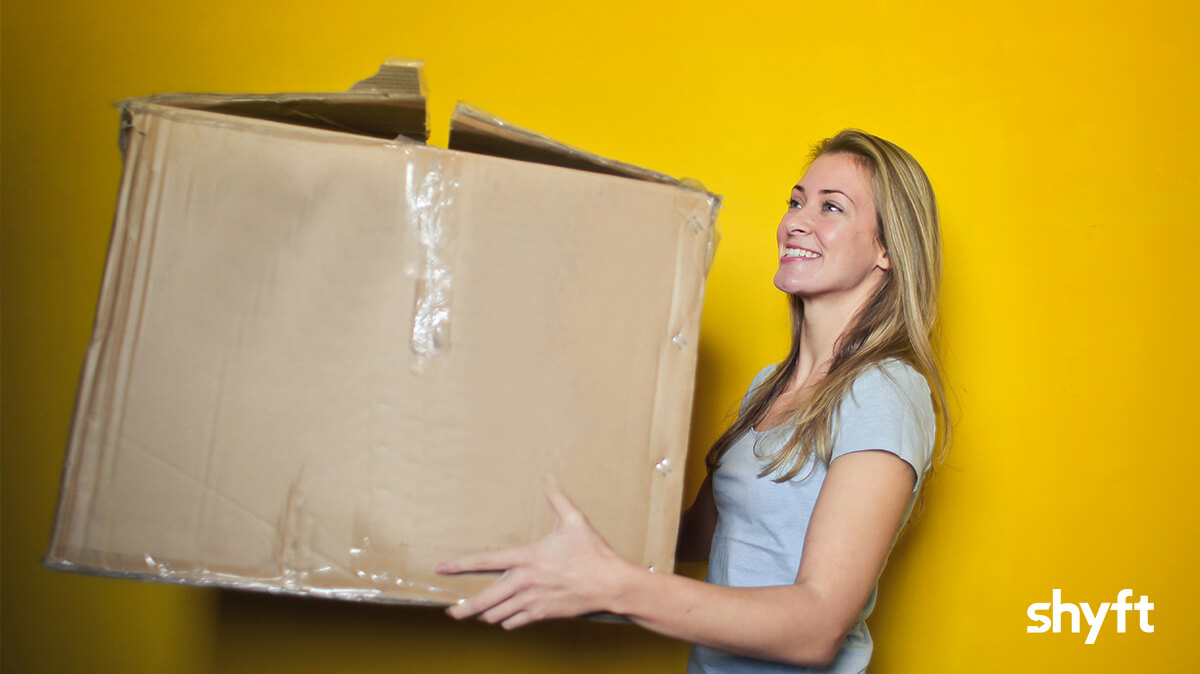 Girl moving a huge box during her relocation