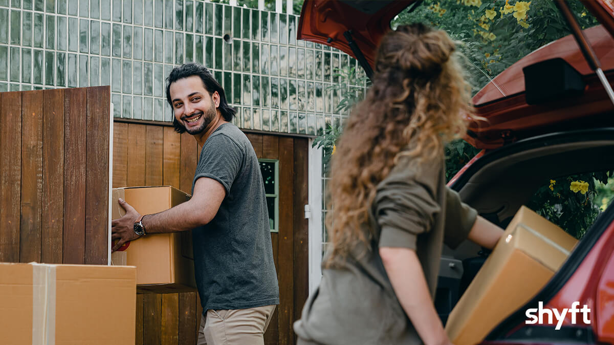 A couple moving, the guy holding a box entering the house and a girl putting a box into the car