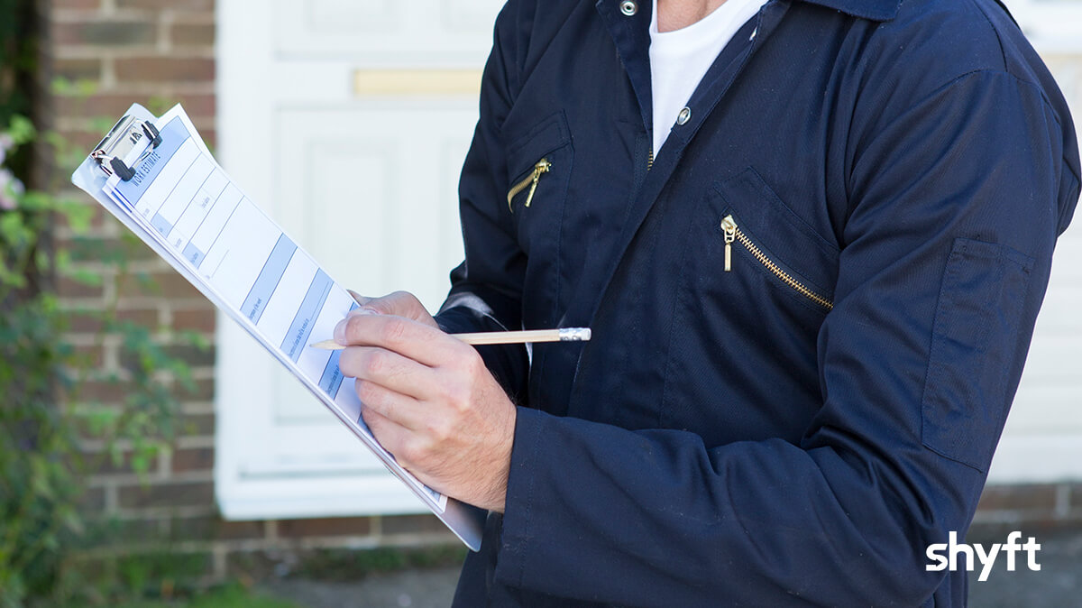 Professional mover filling out a form outside a house
