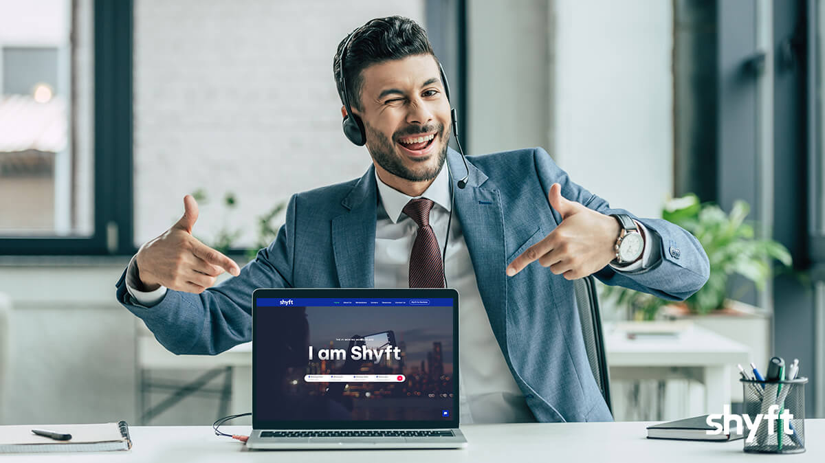 happy Shyft's employee sitting down in an office suit and pointing at a laptop with Shyft's website on