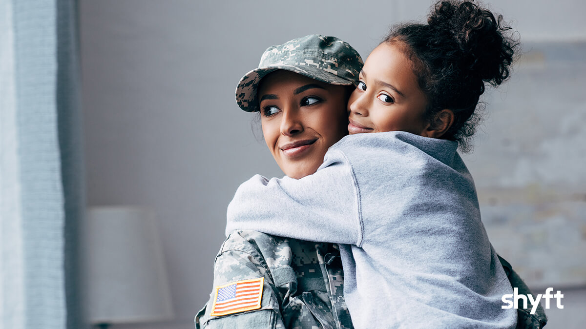 military woman from US army hugging her daughter