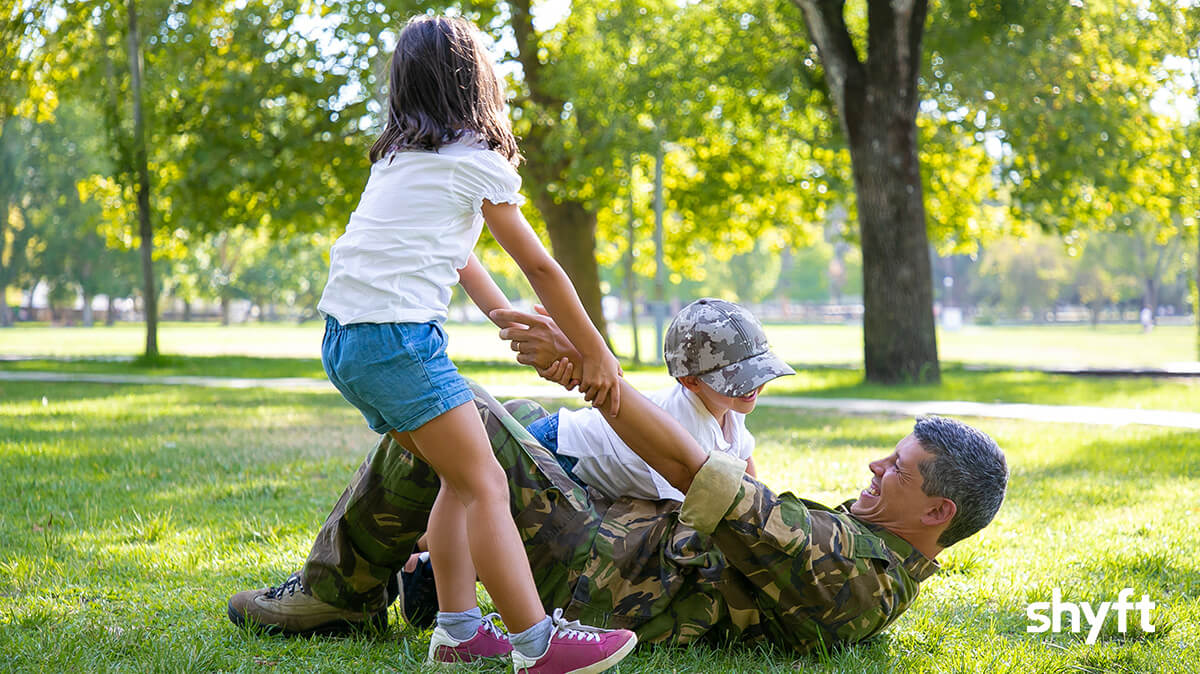 military dad lying on the grass with a smile as his young daughter tries to lift him, playfully and his younger son is lying on top of him