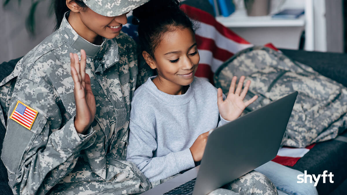 american female soldier with her daughter sitting in front of laptop managing her military relocation