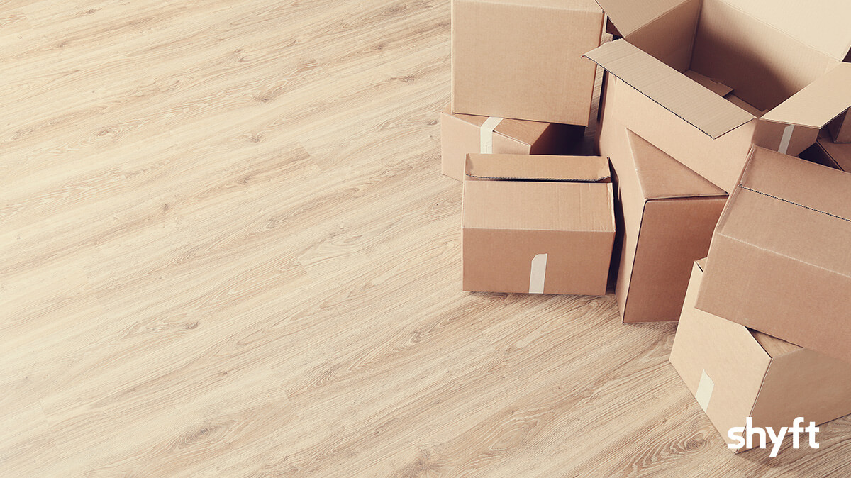 open moving cardboard boxes lying on a wooden, light brown floor