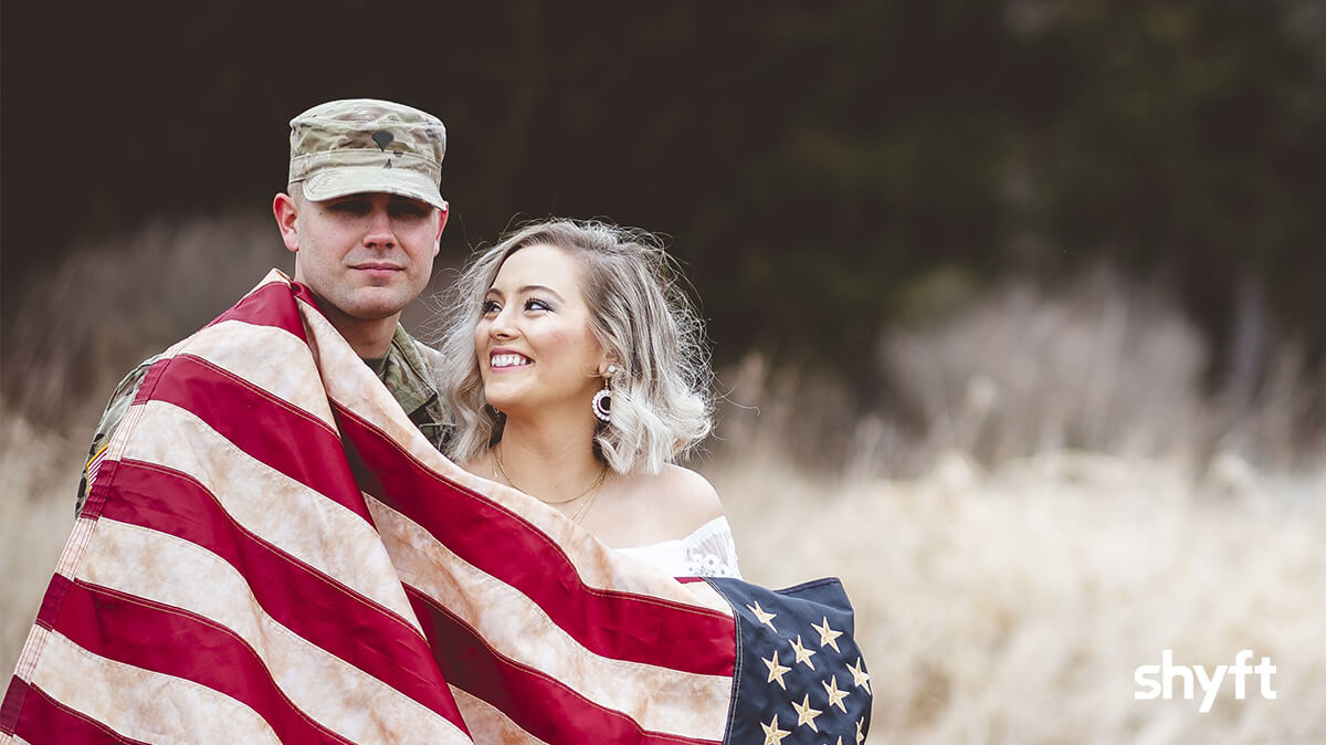a man in military clothes and a woman in a wedding dress, who is looking and smiling at the man, stand in a wheat field with the American flag wrapped around them