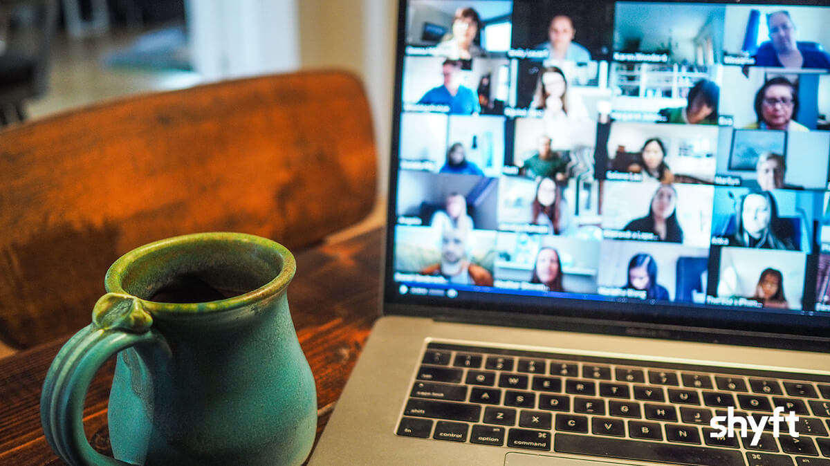 A mug next to a laptop with a zoom video call on with many people