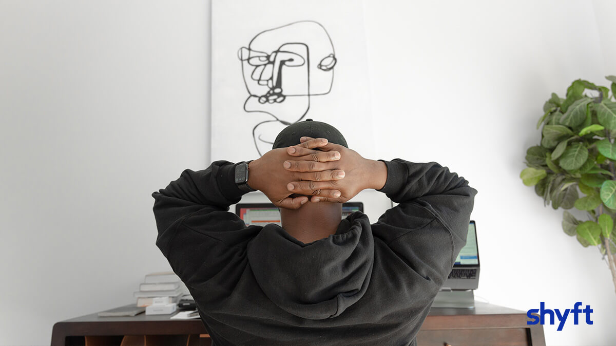 a man with his hands behind his head looking at two laptops, sitting down in front of a desk with a black and white, absurdist painting
