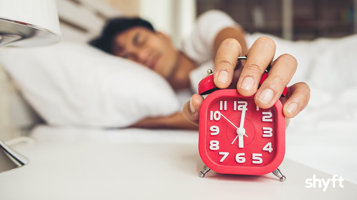 red, alarm clock with a man's hand on top, who is lying in a white bed, with closed eyes, frustrated look on his face