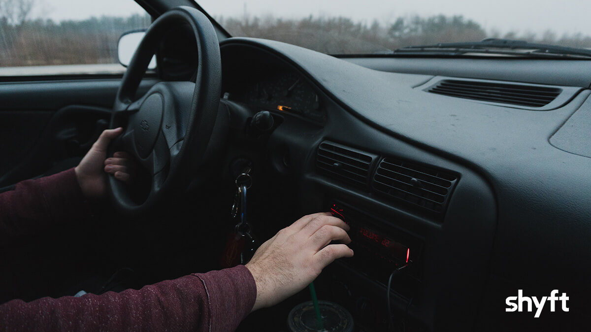 inside a car with dark interior, close up of a man's right hand on the radio, and the left hand on the steering wheel while driving