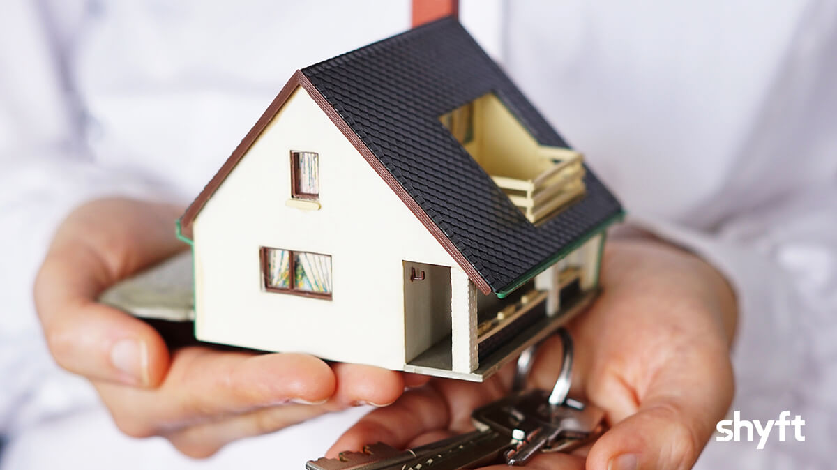 close up of hands holding a tiny house and house keys