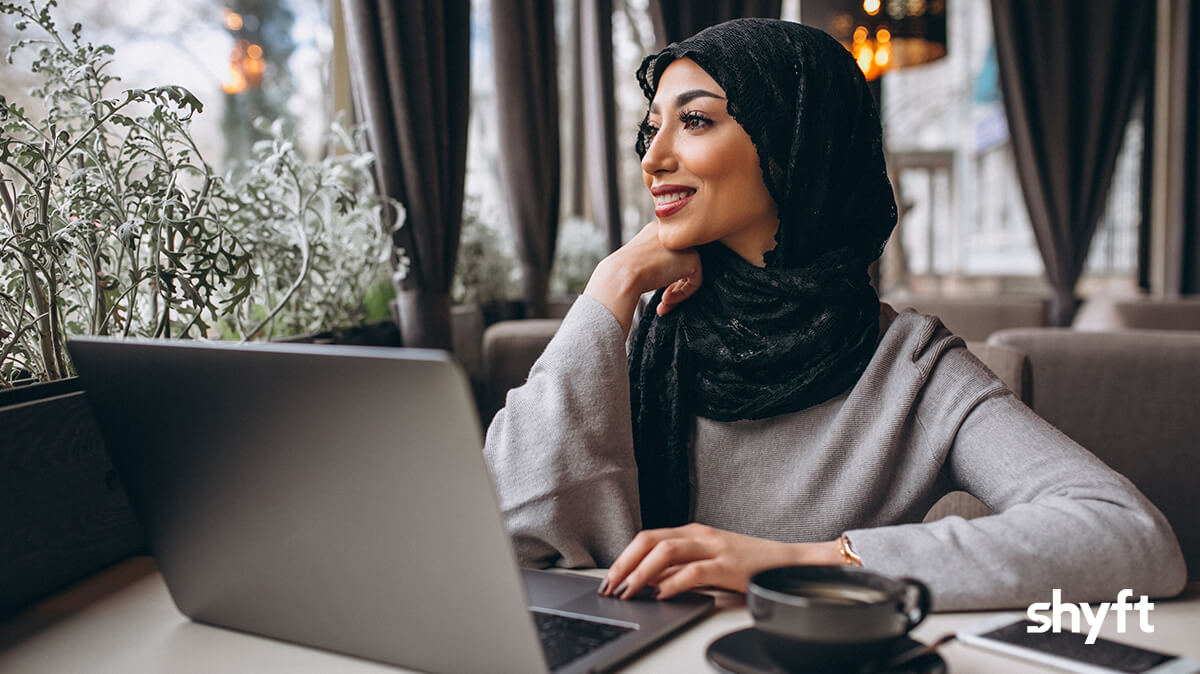 Smiling woman in hijab working from a coffee shop