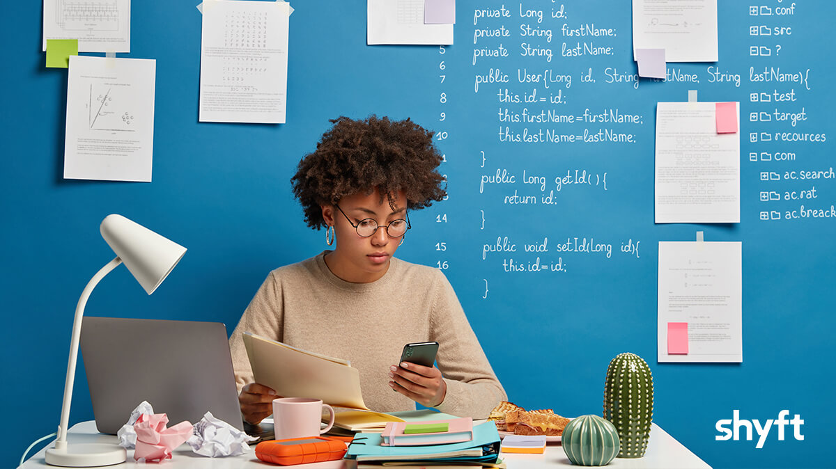 A remote worker at her untidy desk, looking at the laptop while writing notes, she is in front of a blue wall with plenty of notes stuck on it