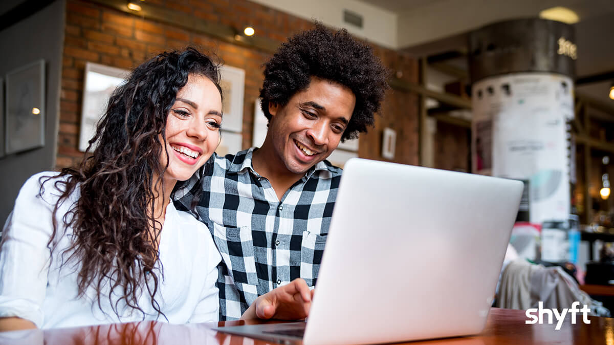 a couple smiling and sitting in a coffee shop, looking at a laptop while searching for interstate movers