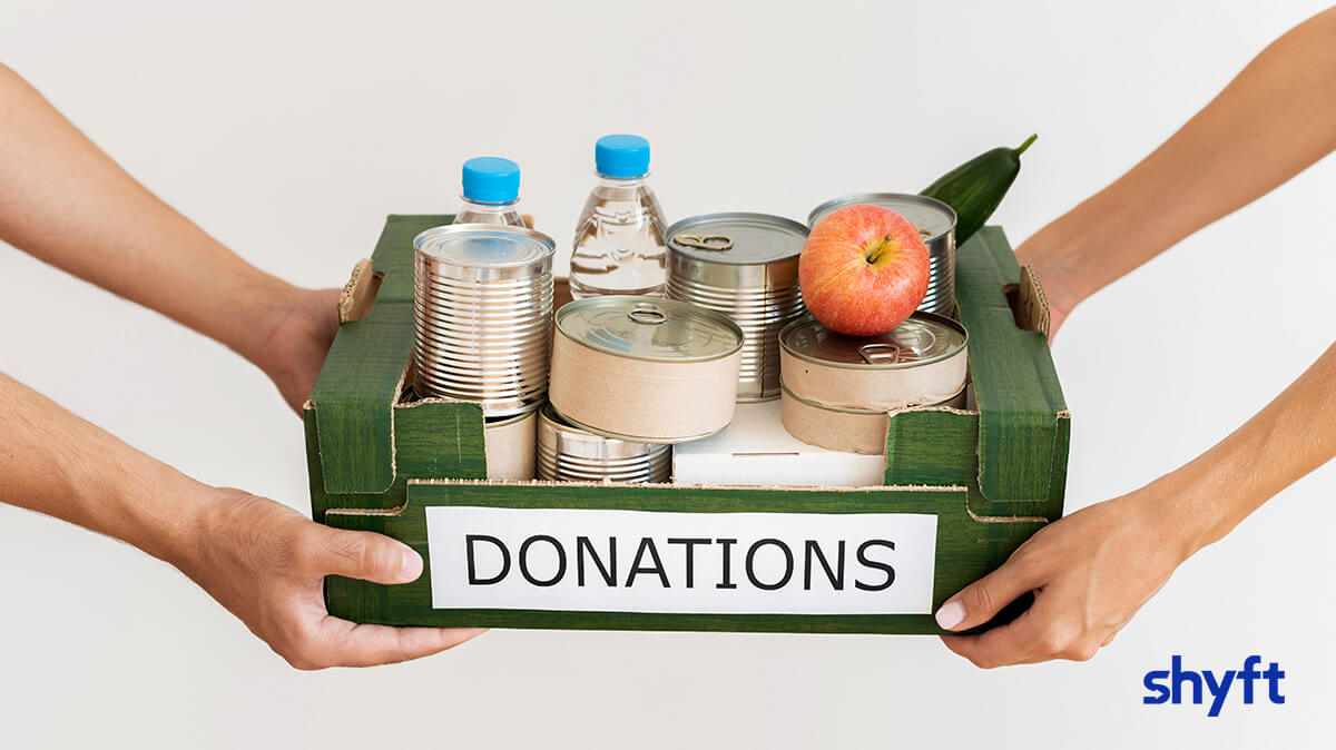 a man and woman holding a green, cardboard box saying ''donations'' filled with food cans, water, an apple and a cucumber inside it