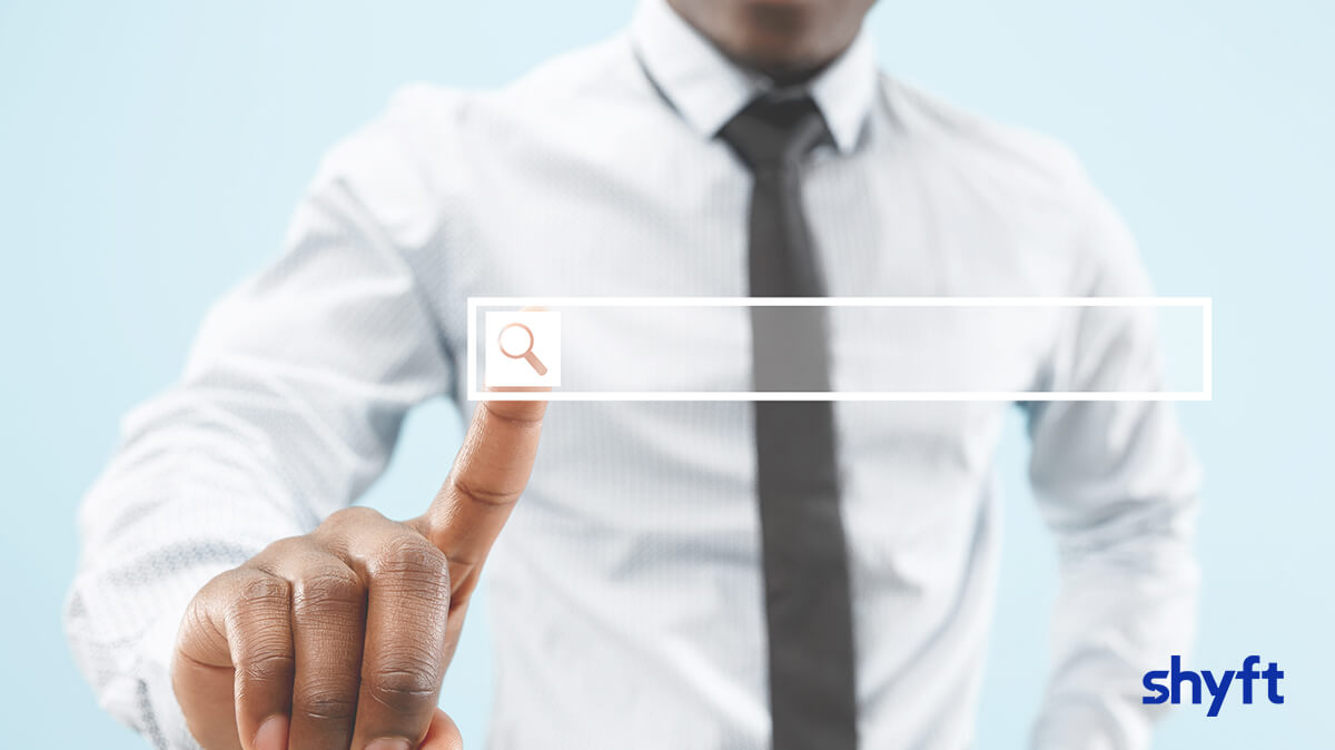 A man in a suit with his hand reaching out and his finger pressing on a floating search bar