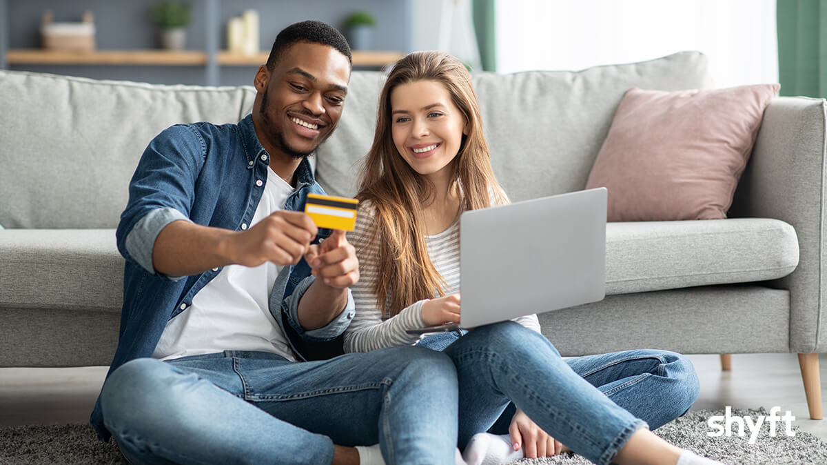 a couple sitting in front of a sofa with the man holding a credit card and the woman has a laptop in her lap