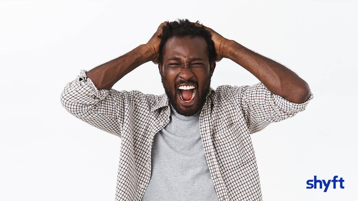 bearded man standing and plucking his hair as he screams out of frustration
