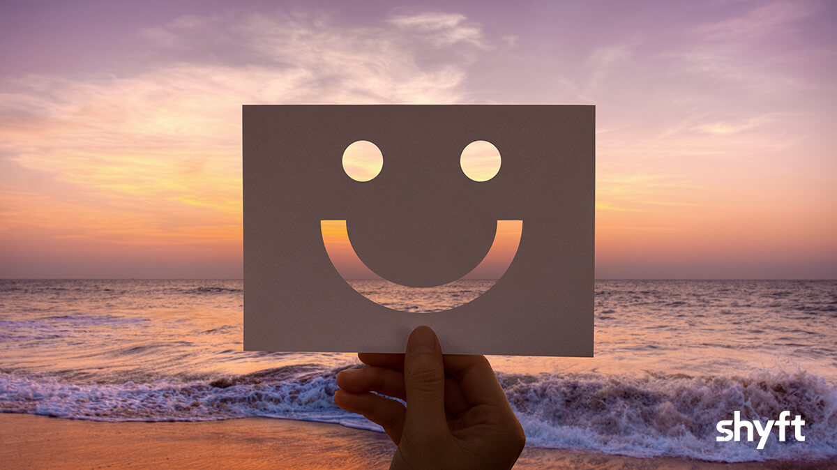 a hand holding up a paper with smiley face on it with the sea in the background