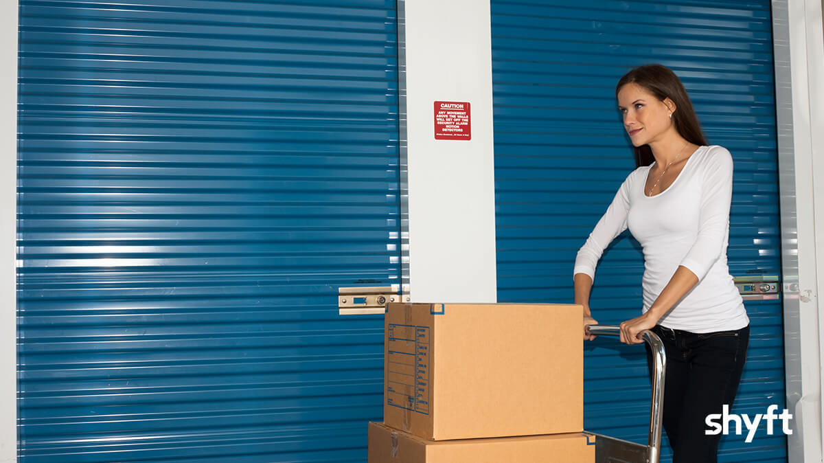 Woman pushing boxes in front of a blue storage unit