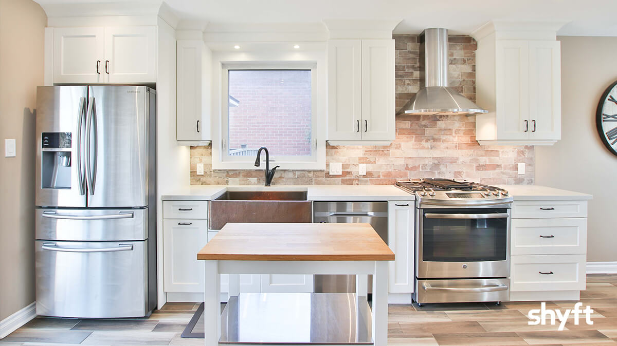A modern kitchen equipped with a kitchen island, silver fridge and silver stove and oven, in white wood counters