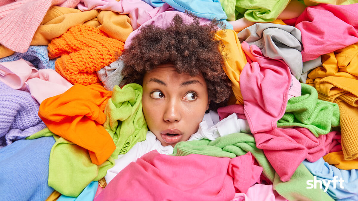 A woman surrounded by different types of clothes, looking concerned on where to donate clothes