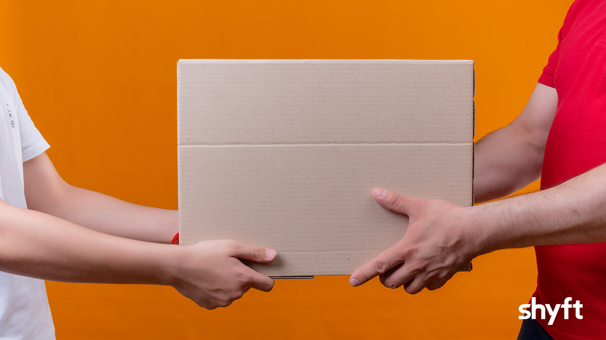 A movers giving a brown moving box to a person who is moving out