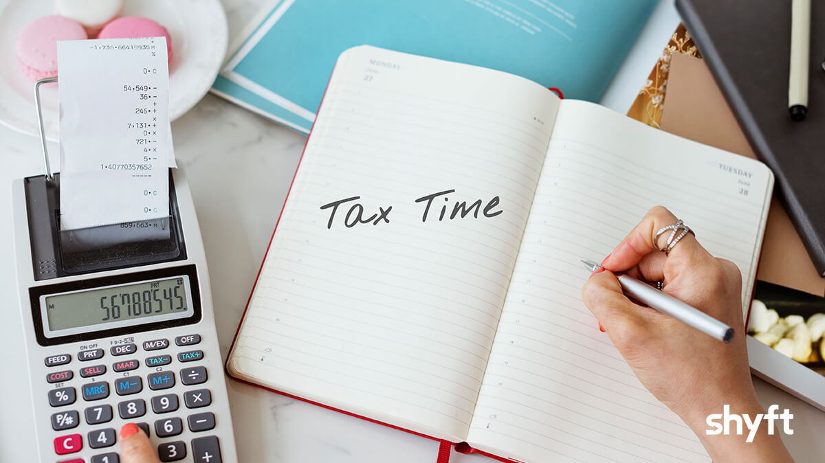 """Bill and calculator on a table with """"tax time"""" written in the notebook"""