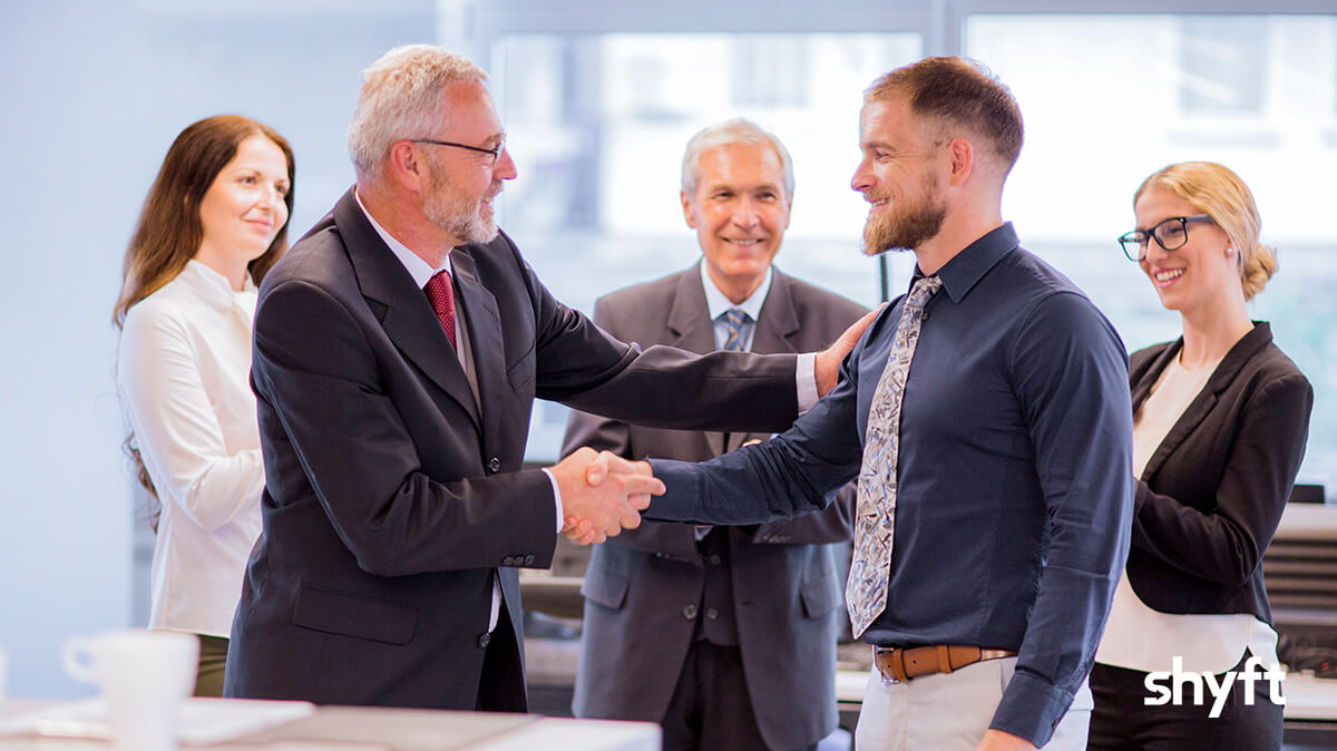 Two businessmen happily shaking hands in front of other smiling people