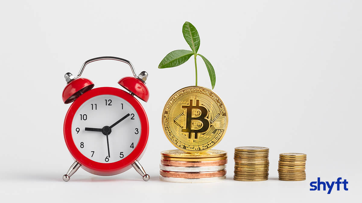 Red alarm clock next to stacks of gold coins with a Bitcoin standing one, with a green plant growing from it
