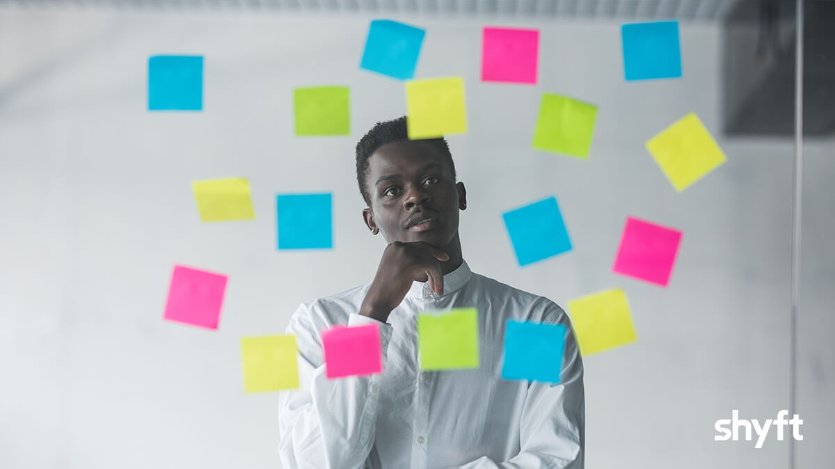 Man standing in front of different colored post-its notes, thinking about his future business plans