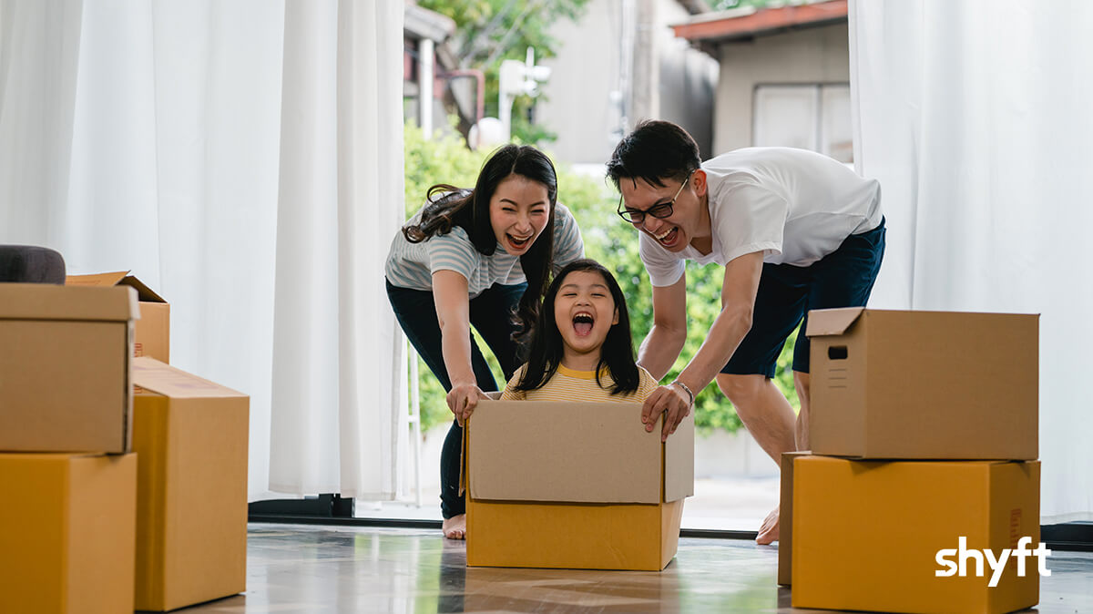 Young mom and dad pushing their daughter in a moving box into their new home