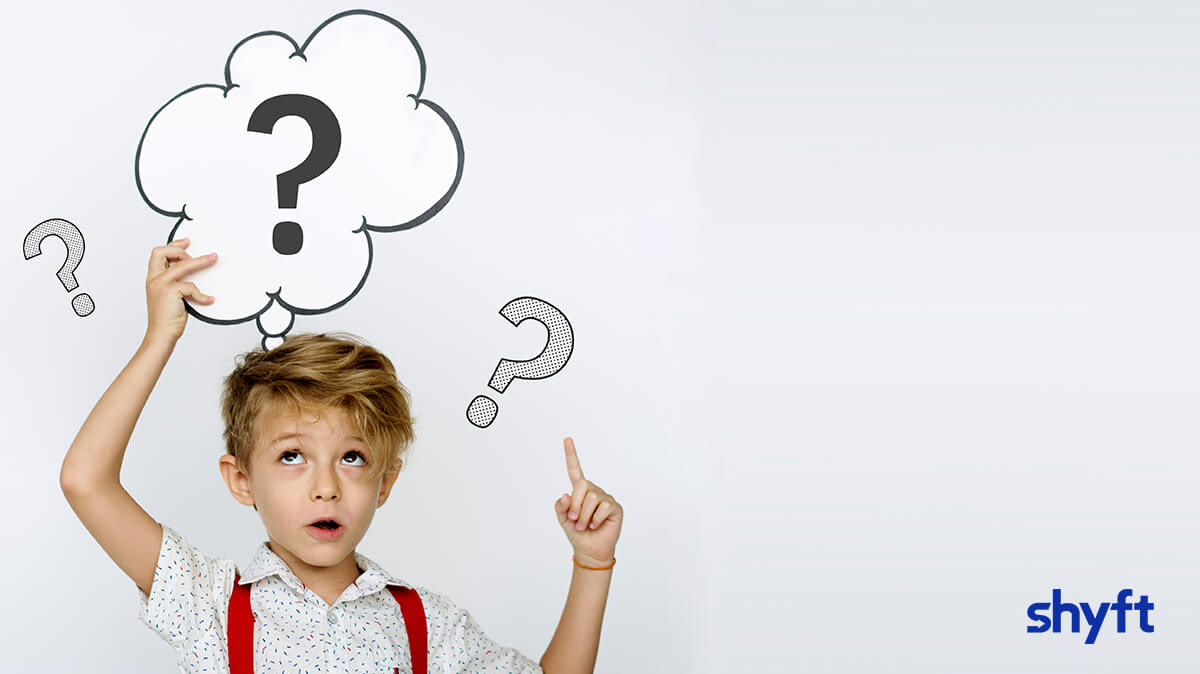 Young boy holding up a thought balloon with a question mark inside and question marks around him
