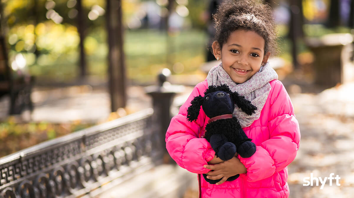 A little girl in pink jacket ready to move hugging her favorite toy