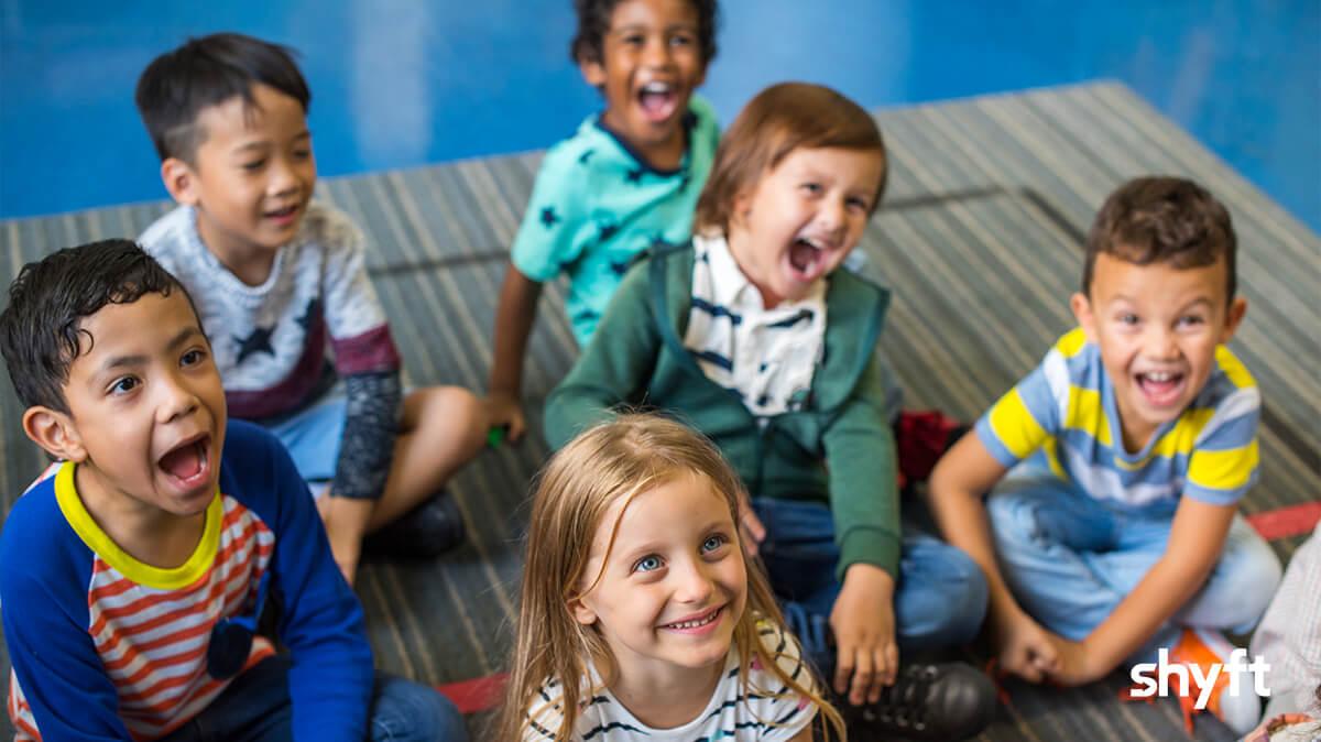 Happy little children sitting on the floor at school