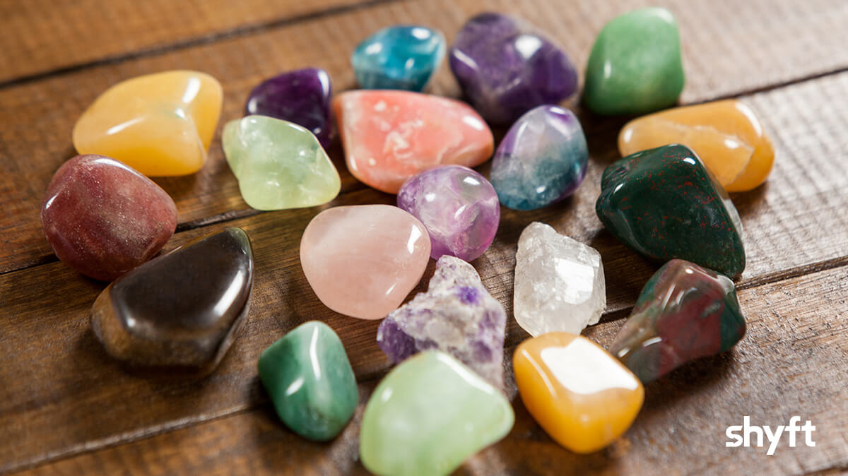 Close up of a group of different color stones on a wooden table
