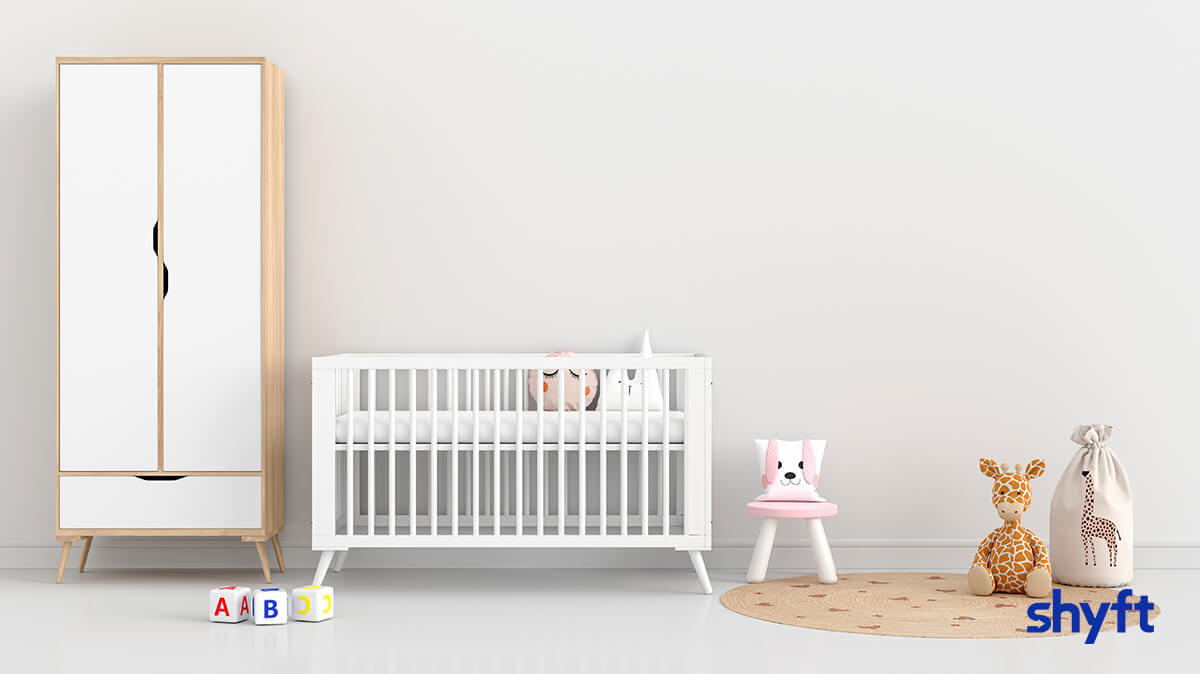 A baby room before the move, with a white closet, a white crib, different toys and a circle carpet on the floor