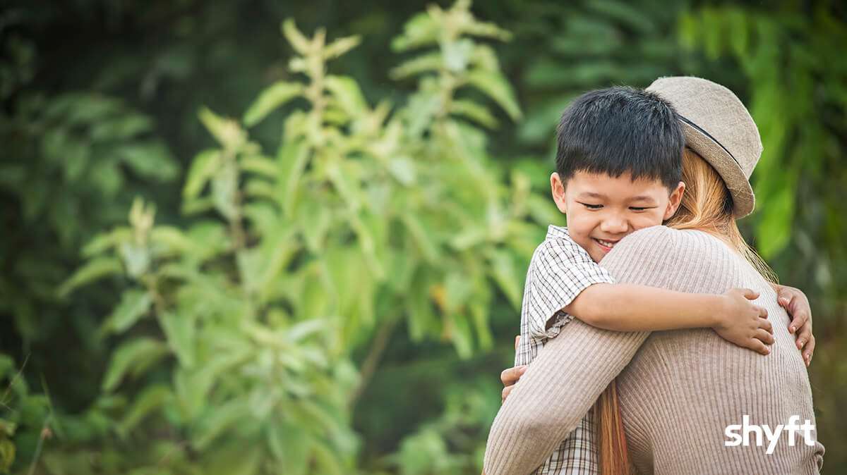 A mom hugging her son outside a green forest, the son is smiling while holding his mom tight