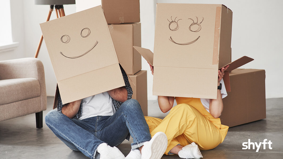 Playful couple sitting on the floor with cardboard boxes over their heads, with smiley faces drawn on them