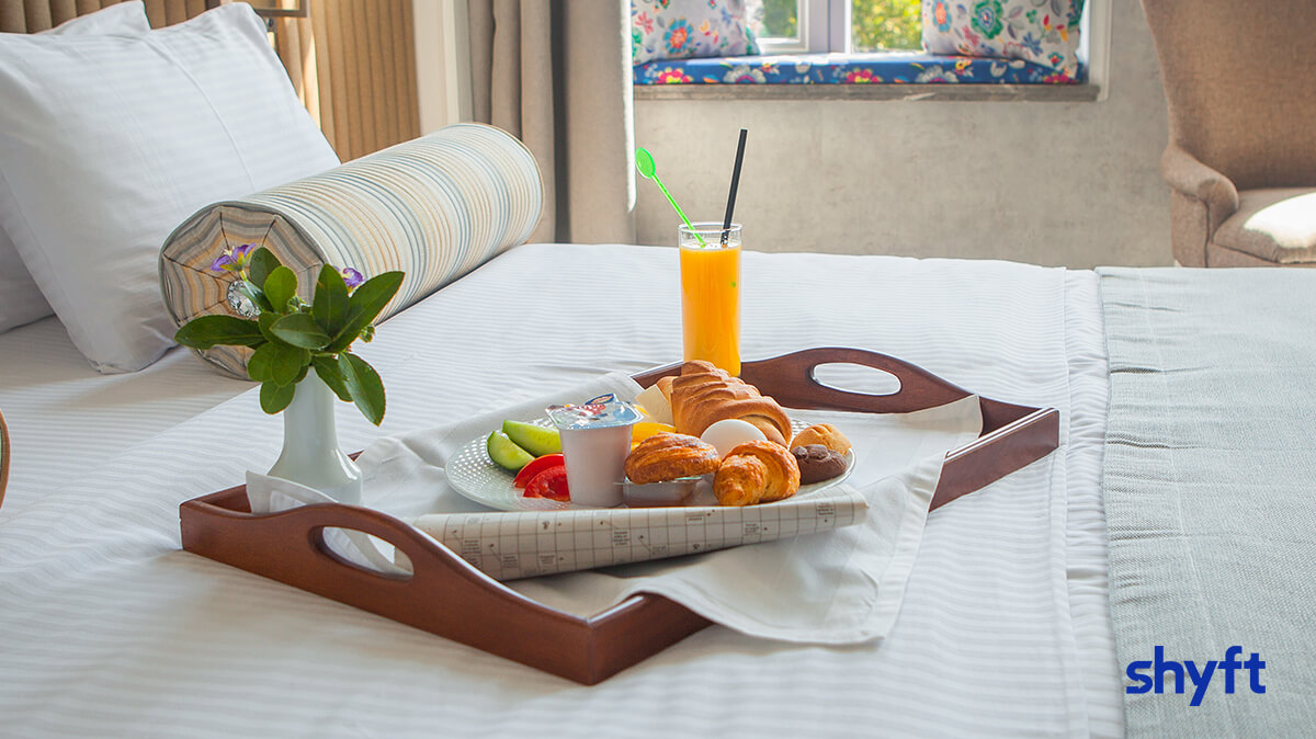 A tray of breakfast on a made, white bed in a hotel room