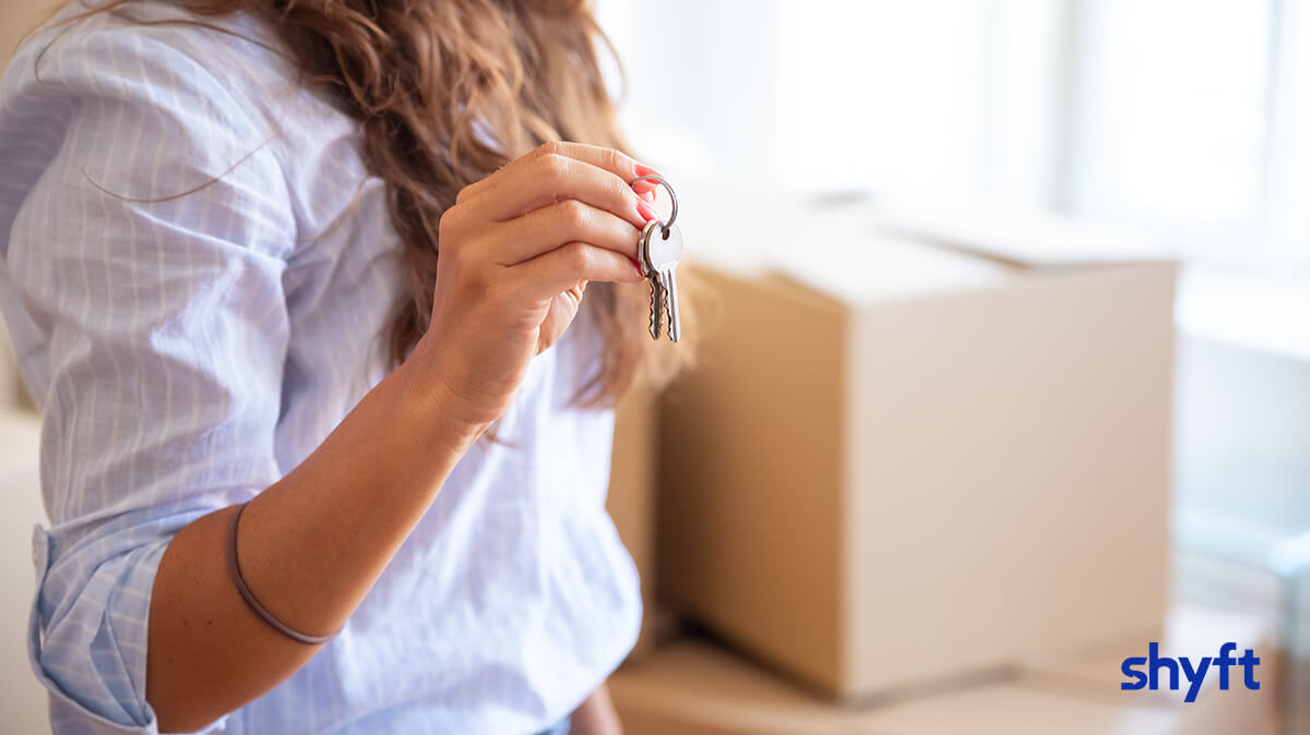 A woman while moving in, holding house keys standing in front of moving boxes