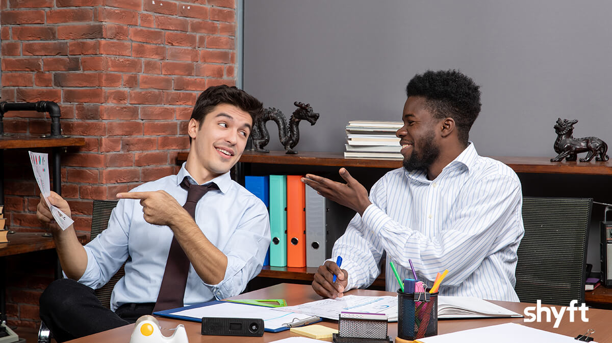 Two men sitting in an office and talking business while both are pointing at a piece of paper that the one is holding up