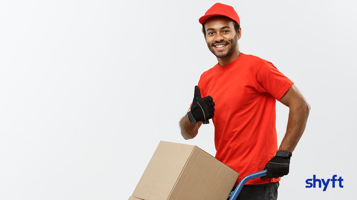 A man in a red shirt and cap moving cardboard boxes, smiling and giving a thumbs up to the camera