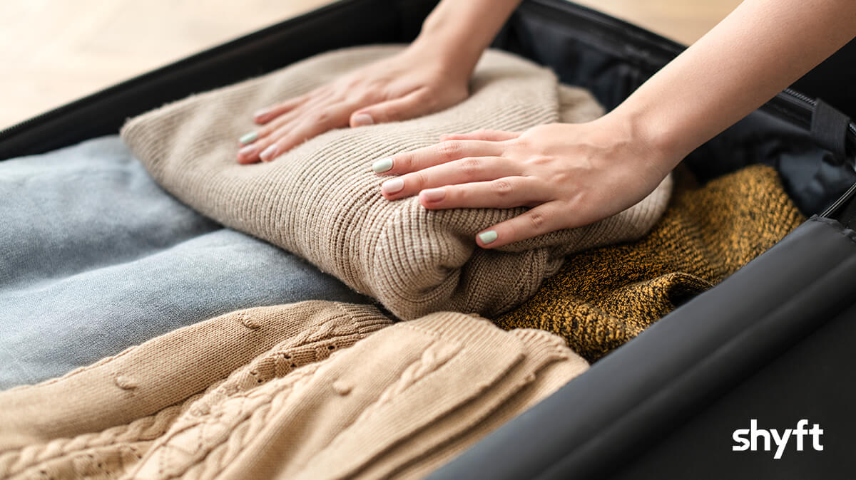 A woman getting ready for a move, packing a suitcase filled with winter clothes