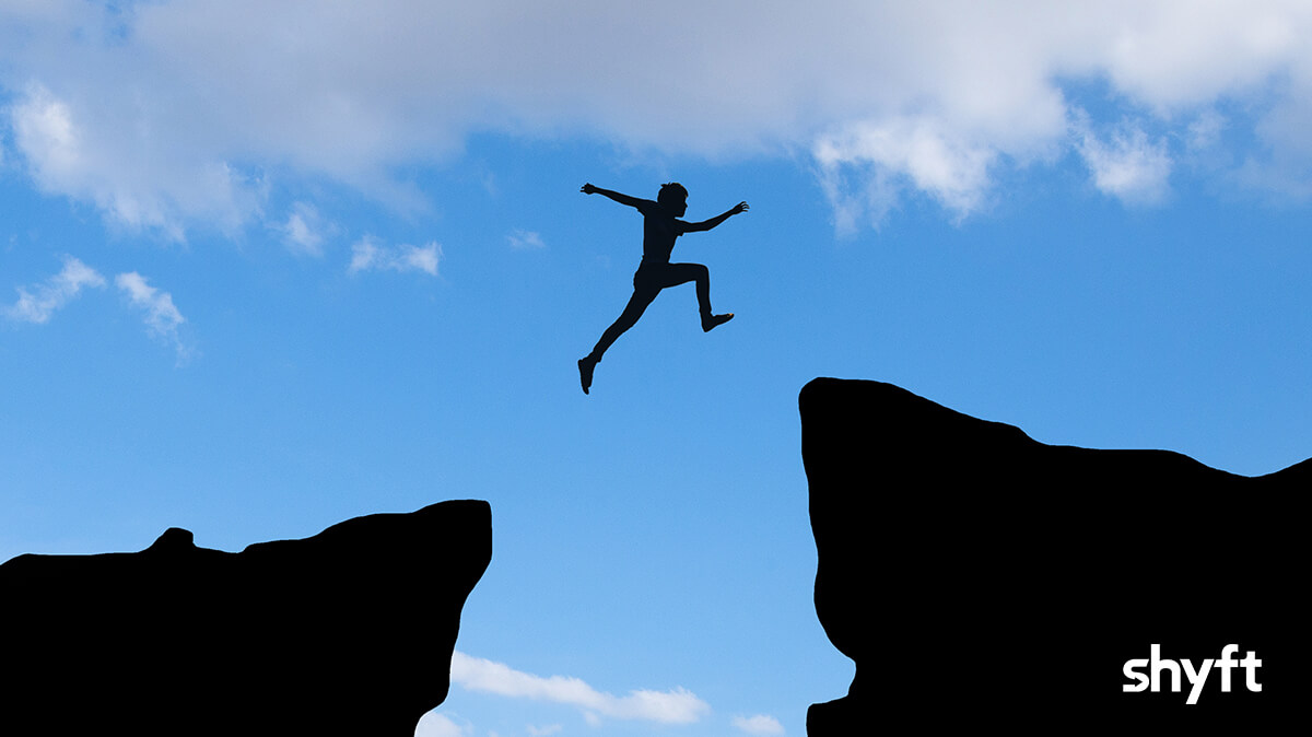 A businessman jumping from one rock to another