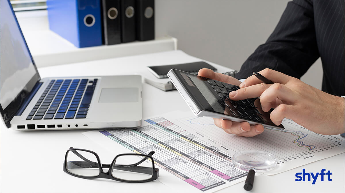 An employee counting the moving expenses on a calculator for his work related relocation