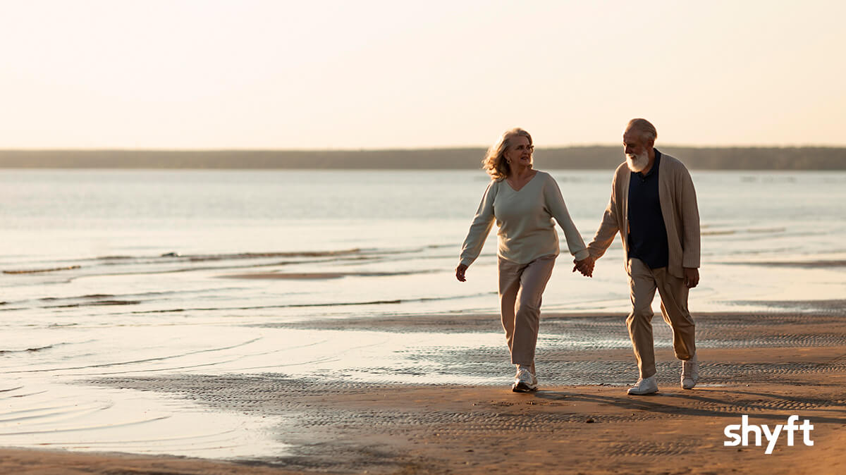 An elderly couple walking on the beach while holding hands