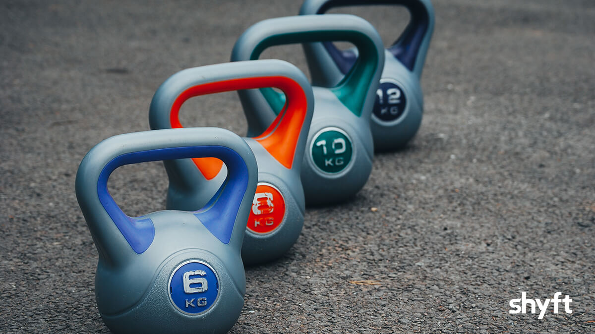 Close up of different sized kettlebells on the gym floor